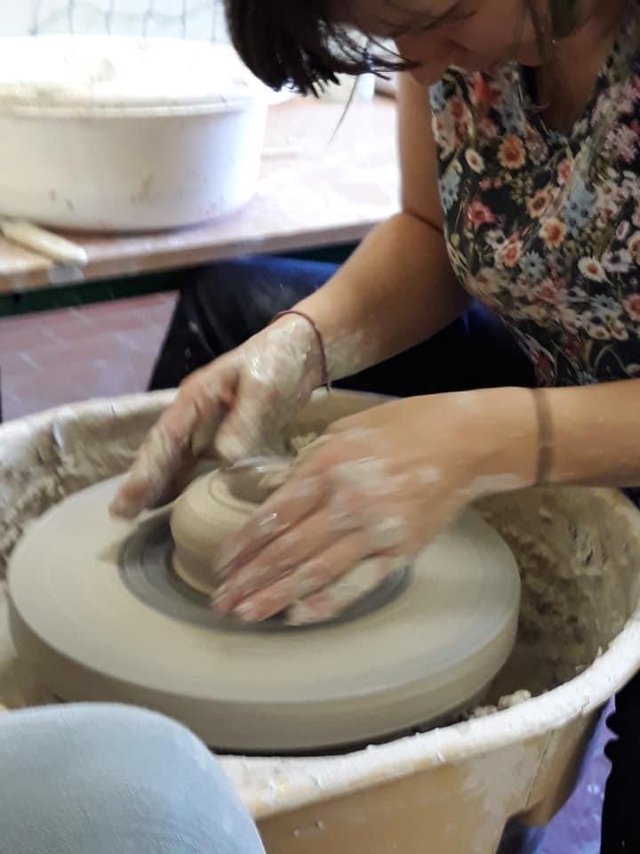 Deux mains pleine d'argile en train de modeler une poterie